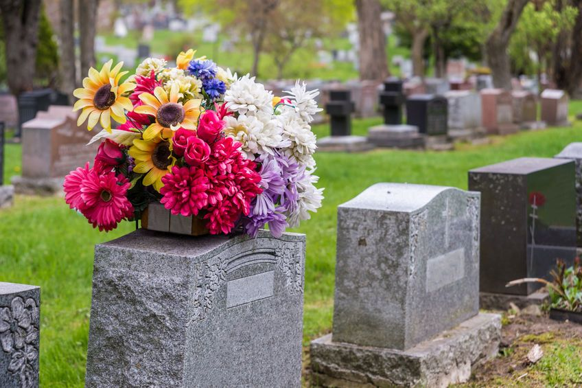Flowers on a tombstone in a cemetary with headstones in the back
